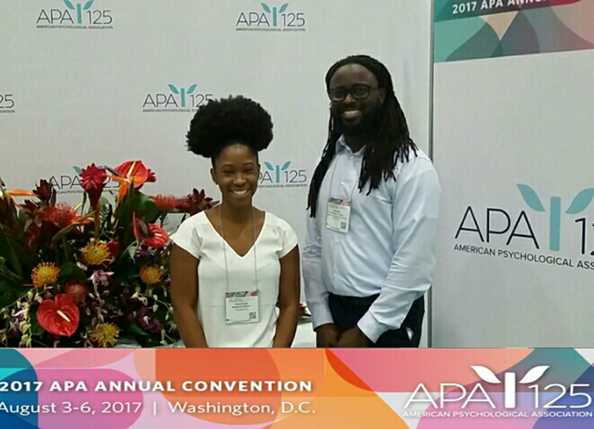 Stephanie and Alfonso pose at the 2017 APA Convention, which was August 3-6 in Washington, D.C. A large urn of flowers is placed nearby.